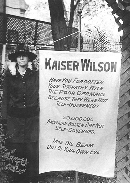 A suffragette with a poster challenging President Woodrow Wilson's hypocrisy (c. 1913) in being alarmed at the Germans' lack of freedom while overlooking women citizens' lack of freedom in his own country.