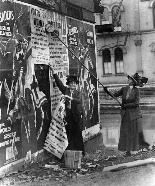 Suffragettes hanging posters advocating women's right to vote.